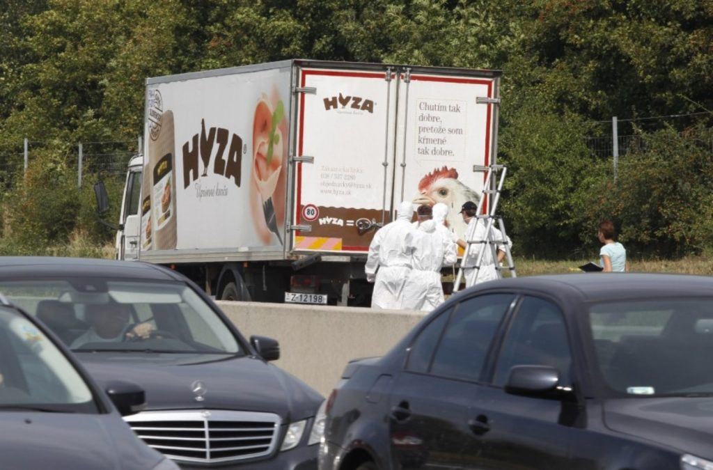 Forensic officers stand in front of a truck inside which where found a large number of dead migrants on a motorway near Neusiedl am See, Austria