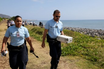 Police officers leave the scene with container holding metallic debris found on a beach in Saint-Denis on the French Reunion Island in the Indian Ocean on August 2, 2015, close to where where a Boeing 777 wing part believed to belong to missing flight MH370 washed up last week.  A piece of metal was found on La Reunion island, where a Boeing 777 wing part believed to belong to missing flight MH370 washed up last week, said a source close to the investigation.  Investigators on the Indian Ocean island took the debris into evidence as part of their probe into the fate of Malaysia Airlines flight MH370, however nothing indicated the piece of metal came from an airplane, the source said.  AFP PHOTO / RICHARD BOUHET