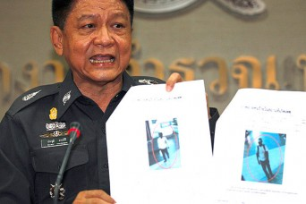 Thai police Lieutenant General Prawut Thavornsiri shows pictures of what the police say are two suspicious-looking people caught on CCTV footage whom they are trying to identify in relation to the bombings.