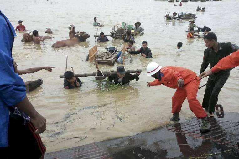 Myanmar rescue workers assist victims with their cattle to flee flooded areas near Thayet