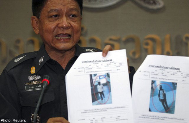 Thai police Lieutenant General Prawut Thavornsiri shows pictures of what the police say are two suspicious-looking people caught on CCTV footage