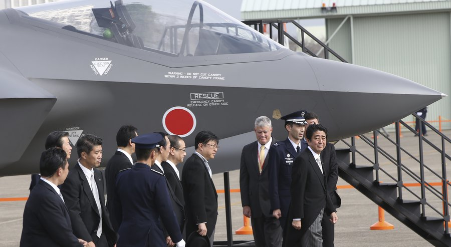Japanese Prime Minister Shinzo Abe, far right, walks past a mock-up of the F-35 fighter jet