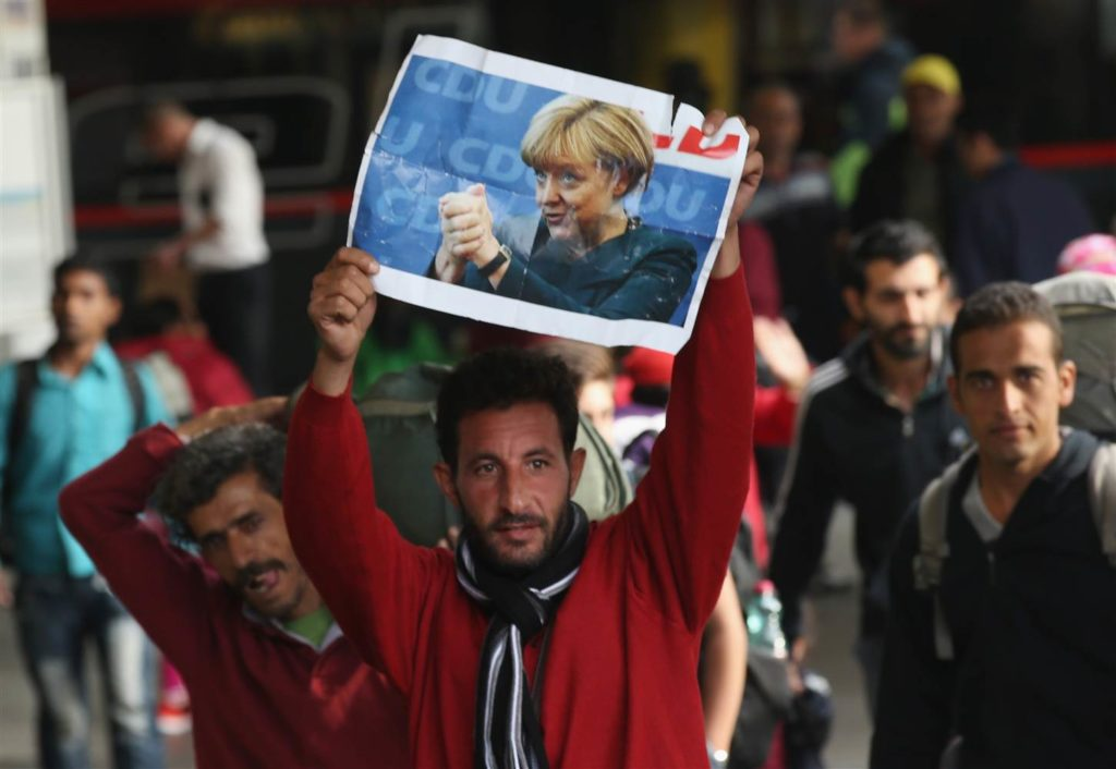 A migrant arriving in Germany holds a picture of Angela Merkel