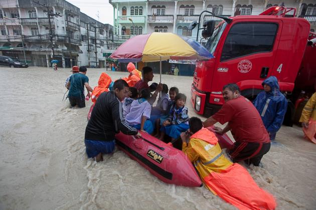 Rescue workers use an inflatable boat to bring schoolchildren home from their flooded school
