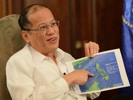 Philippine President Benigno Aquino points to a copy of China's nine-dash line map