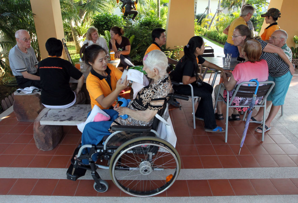 "Alzheimer patients from Switzerland are cared by Thai caretakers during afternoon activities at Baan Kamlangchay care center in Chiang Mai province, northern Thailand. Thailand is poised to attract more Alzheimer's sufferers from the Alpine country and elsewhere. In this pleasant city ringed by mountains ""Baan Kamlangchay"" will be followed by a $10 million dollar, holiday-like home scheduled to open before mid-2014 and a small Alzheimer's unit within a retirement community set on the grounds of a former four-star resort. (AP Photo/Apichart Weerawong)"