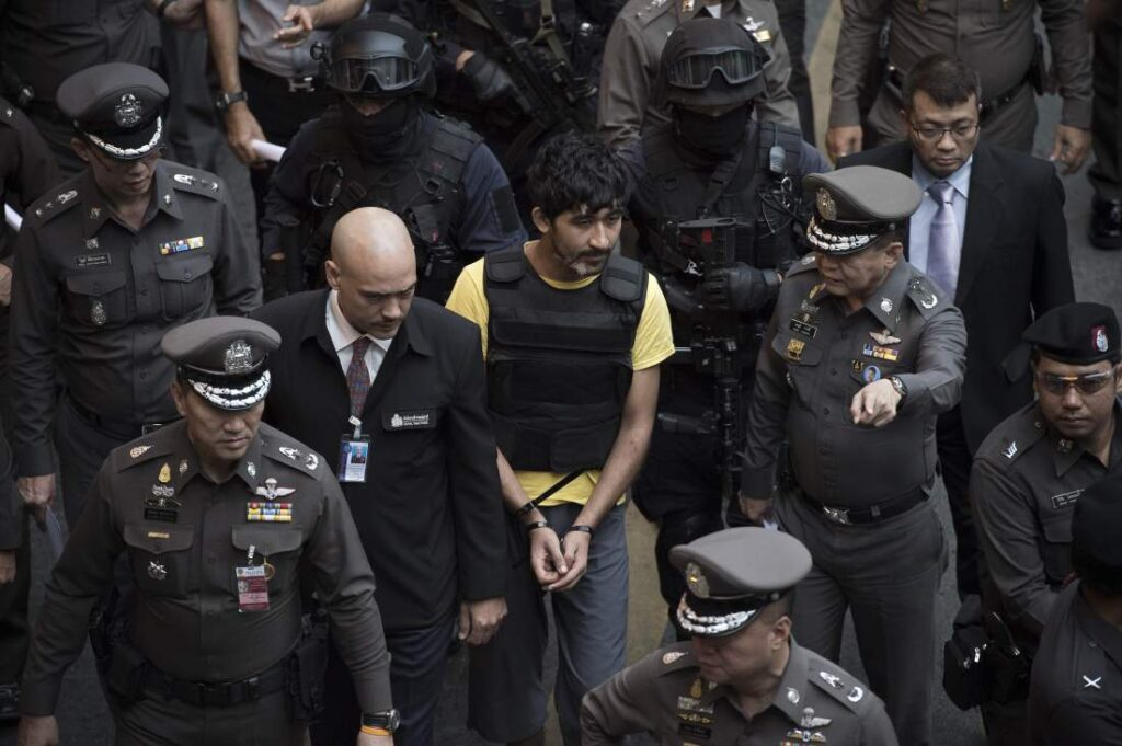 A foreign suspect in the August 17 Erawan shrine bombing, identified by the ruling junta as Yusufu Mieraili (C, in yellow), is seen during a reenactment with police officers outside the Central World department store nearby the Erawan shrine (not pictured) in Bangkok on September 9, 2015. A key suspect in last month's deadly Bangkok blast handed the backpack bomb over to a man in a yellow T-shirt later seen placing it at a busy shrine, Thai police said. Mystery surrounds the motive of the alleged network behind the August 17 bombing that left 20 people dead in the heart of Bangkok and rocked Thailand's key tourist industry. AFP PHOTO / Nicolas ASFOURI        (Photo credit should read NICOLAS ASFOURI/AFP/Getty Images)