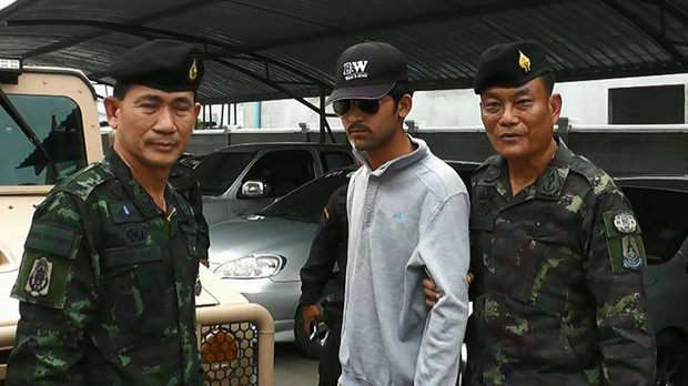 Thai police escort a suspect (centre) arrested on the Thai side of the Cambodian border on 1 September in connection with the bomb attack in Bangkok