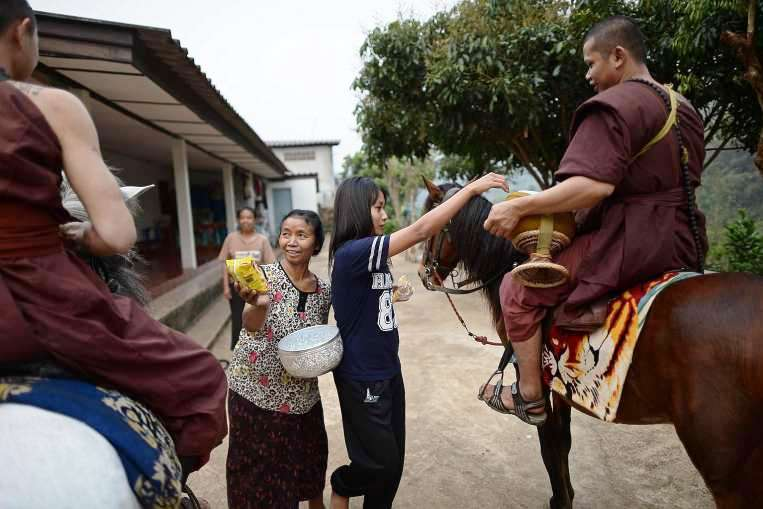 """Residents offering alms to horse-riding monks during their early morning alms-collecting round around the """"Temple of the Golden Horse"""""""