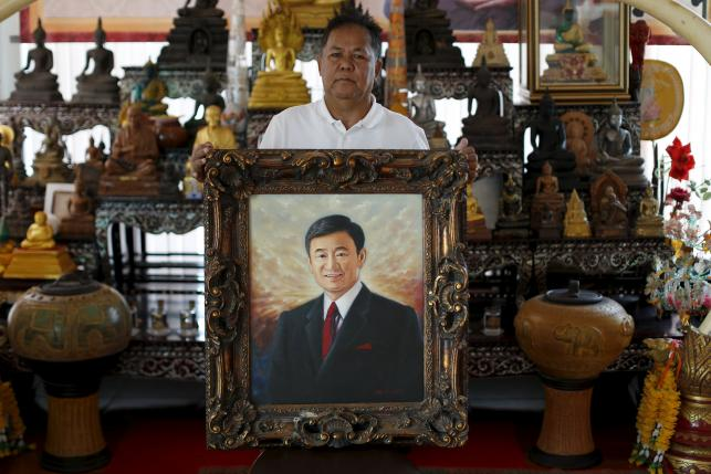 Red shirt movement leader Kwanchai Praipana poses with a photo of former PM Thaksin Shinawatra at his office in Udon Thani, Thailand, September 15, 2015. REUTERS/Jorge Silva