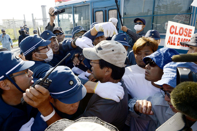 Protesters scuffling with the police as they try to demonstrate outside Camp Schwab, an existing American base in Okinawa in southern Japan.