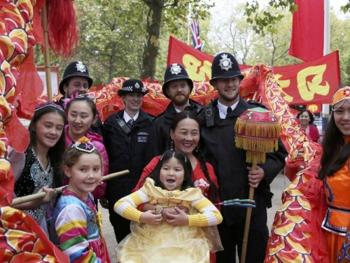 Supporters of China's President Xi Jinping pose for a picture with police officers as they wait on the Mall for him to pass during his ceremonial welcome