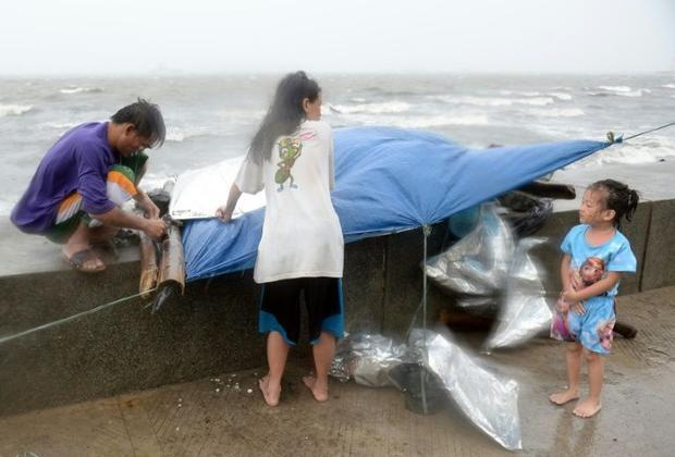 A family fix their temporary shelter during heavy wind and rains brought on by Powerful Typhoon Koppu along Roxas boulevard in Manila