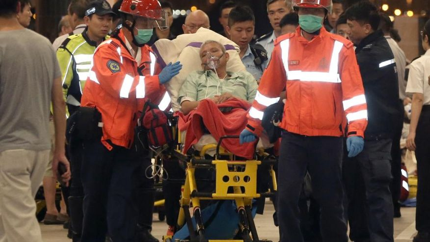 An injured passenger of a high-speed ferry is escorted by rescuers to a hospital after getting on shore in Hong Kong Monday,