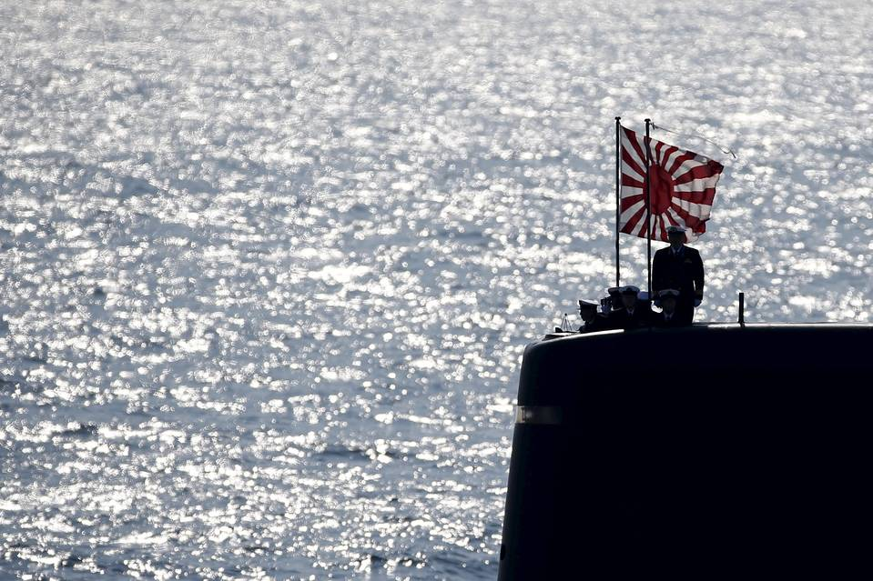 Officials stand aboard a Japanese submarine during Sunday's fleet review. Toru Hanai/Reuters Japan Maritime Self-Defense Force ship Kurama appears from the smoke during a fleet review in
