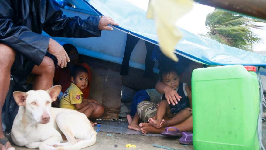 A family seeks shelter under a plastic sheet by a concrete wall amid strong wind and a slight rain brought by Typhoon Koppu Sunday