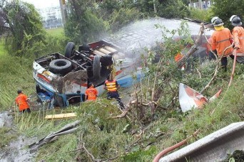 Rescuers prepare to bring injured passengers from the overturned bus. (Photo by Prasit Tangprasert)