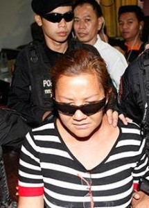 Poranee Napadol, 48, is escorted by police after being arrested Friday