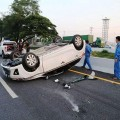 oyota Yaris lies upside down after hitting a cow that fell from a truck