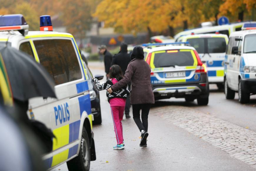 A student and her parent leave a school in Trollhattan, Sweden, on Thursday. A masked man wielding 'knife-like weapons' killed one teacher and wounded at least two students at the school before being shot by police.
