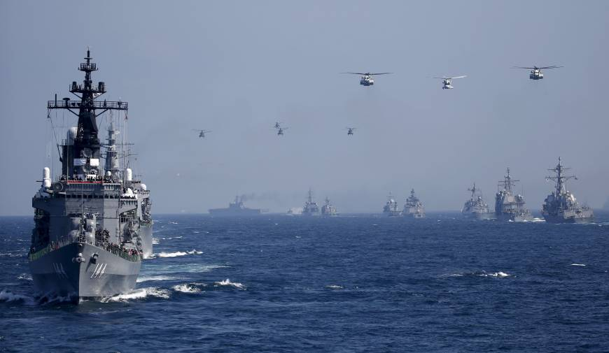 The Maritime Self-Defense Force destroyer Kurama (left) carrying Prime Minister Shinzo Abe leads other vessels and helicopters during a fleet review in Sagami Bay off Yokosuka
