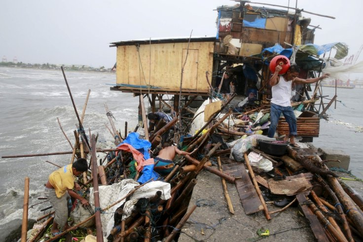 Family attempts to salvage items from home damaged by Typhoon Koppu