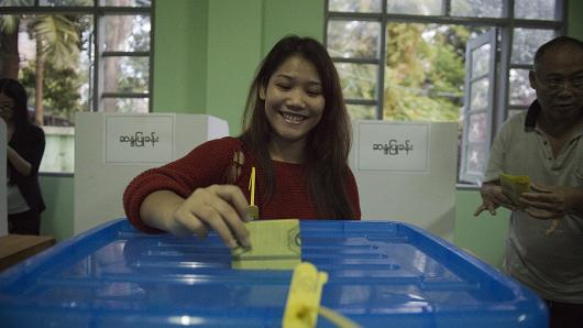 A woman casts her vote at a polling station in Tachilek on November 8, 2015