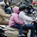 Motorcyclist bundle up as temperatures drop in Chiang Rai