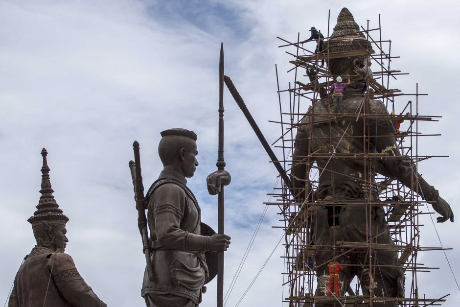 Labourers work on the giant bronze statue of former King Ram Khamhaeng (R) in Hua Hin, Thailand