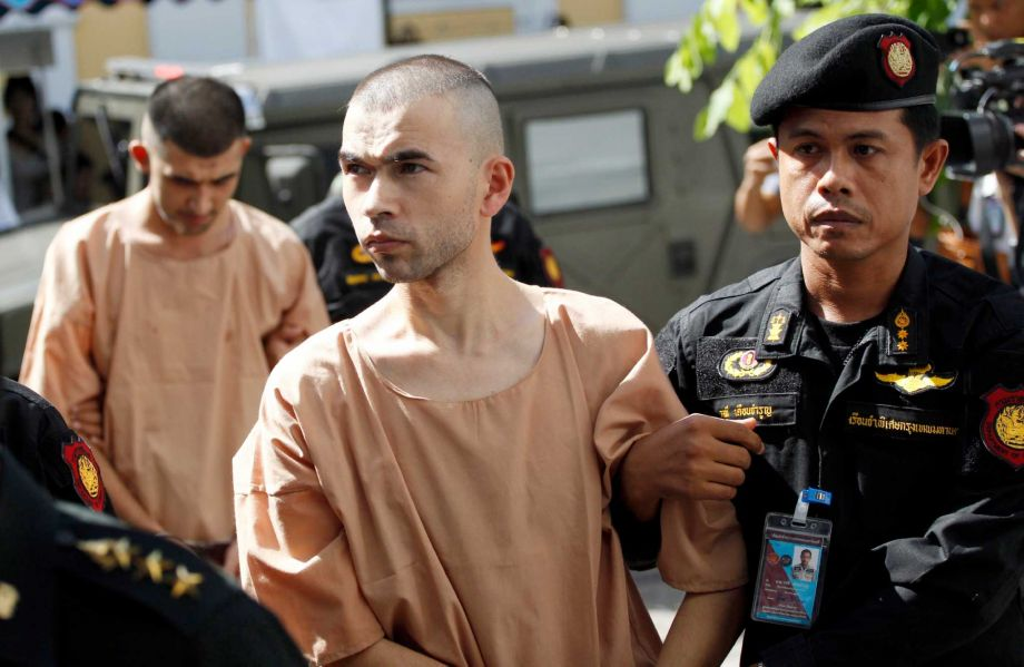 Police officers escort suspects in the Aug. 17 blast at Erawan Shrine, Bilal Mohammad, front, and Mieraili Yusufu, rear, as they arrive at a military court in Bangkok
