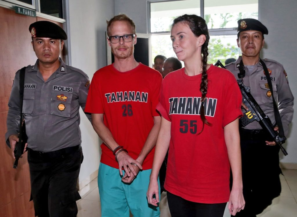 British journalists Neil Bonner, second left, and Rebecca Prosser, right, are escorted by armed police officers after their sentencing hearing at the local district court in Batam, Indonesia,