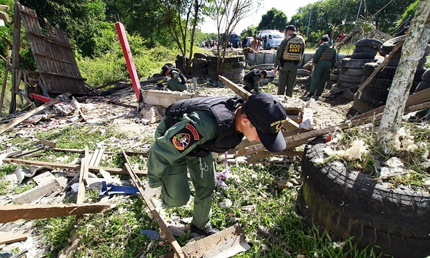 Troops inspect the site of a bomb blast in Khok Pho, Thailand