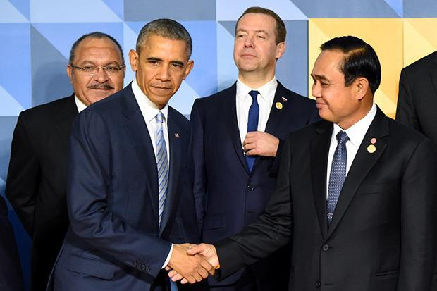 US President Barack Obama shakes hands with Prime Minister Prayut Chan-o-cha as they get in position for a group photo with other leaders at the Asia-Pacific Economic Cooperation summit in Manila