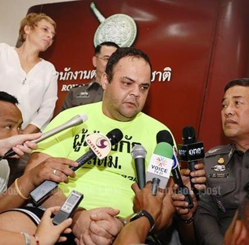 Frenchman Andre Cabau (in yellow shirt) is interviewed by reporters at a news conference on Monday