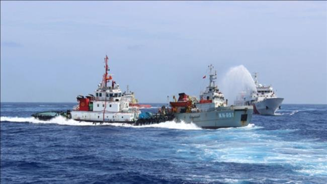Chinese vessel ramming a Vietnamese boat while another Chinese ship fires water cannon on it in the South China Sea.
