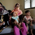 Pakistani refugees sit in a temporary room after being released on bail in Bangkok