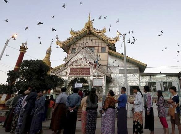 People line up outside a Buddhist prayer hall to vote during the general election in Mandalay, Myanmar