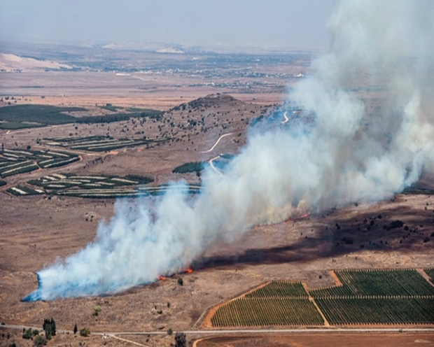 smoke billowing from what was described as the crash site of a plane after it was shot down near the Turkish-Syrian border