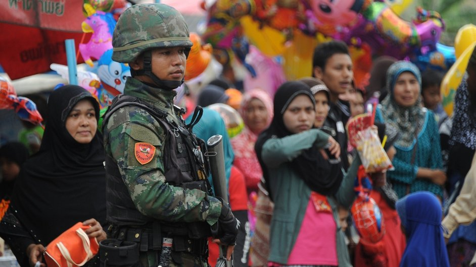 Thai soldiers stand guard next to Muslim villagers during a local festival in Narathiwat province Thailand