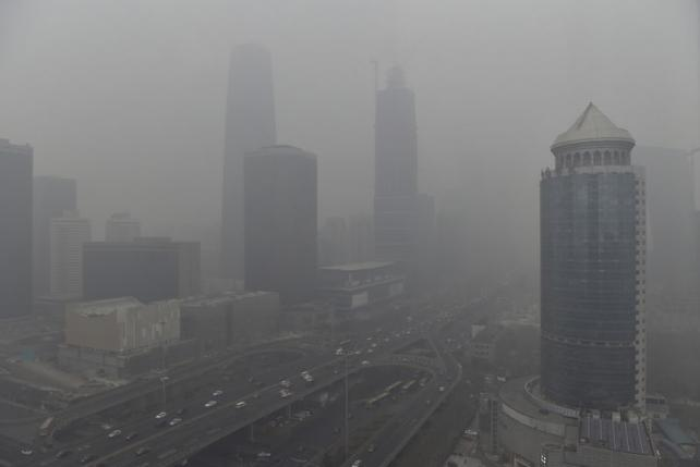 "Vehicles travel on the Guomao bridge (bottom L) as the Central Business District (CBD) area is seen amid heavy smog after the city issued its first ever ""red alert"" for air pollution, in Beijing, China, December 8, 2015. REUTERS/Stringer"