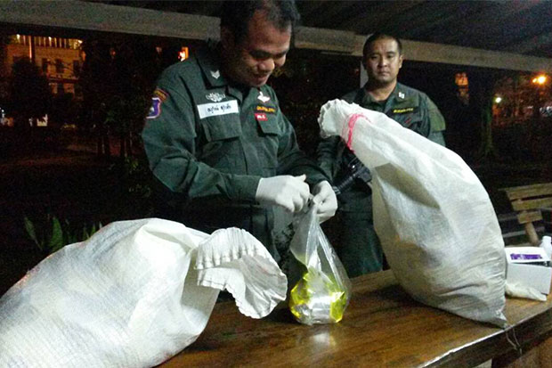 Officers examine two fertiliser sacks abandoned by drug traffickers and find 20kg ofcrystal methamphetamine hidden inside. (Photo by Chinpat Chaimon)