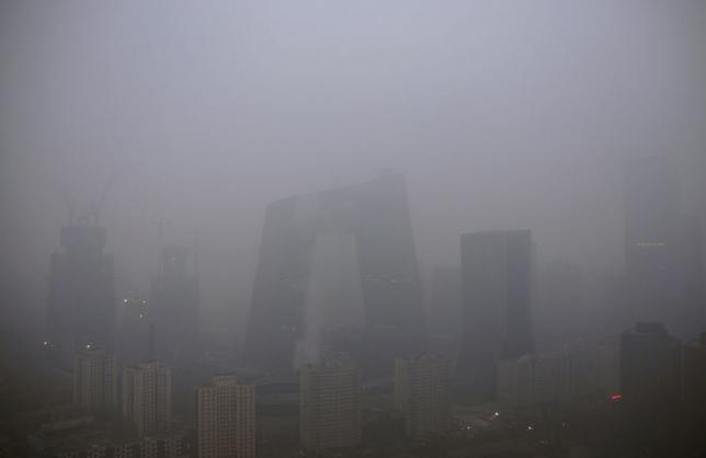 "The China Central Television (CCTV) building and the Central Business District (CBD) area are seen amid heavy smog after the city issued its first ever ""red alert"" for air pollution, in Beijing, China, December 8, 2015. REUTERS/Stringer"