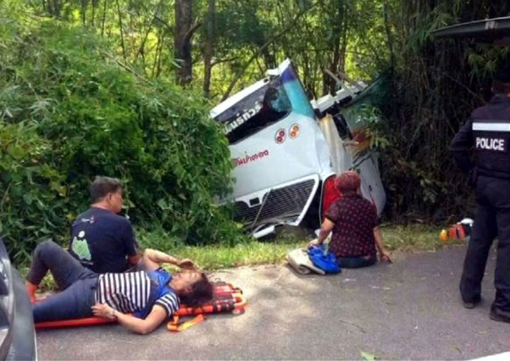Injured Malaysian tourists wait for medical treatment next to a Thai police officer after a tourist bus crashed on a mountain roadside of Doi Saket district, Chiang Mai
