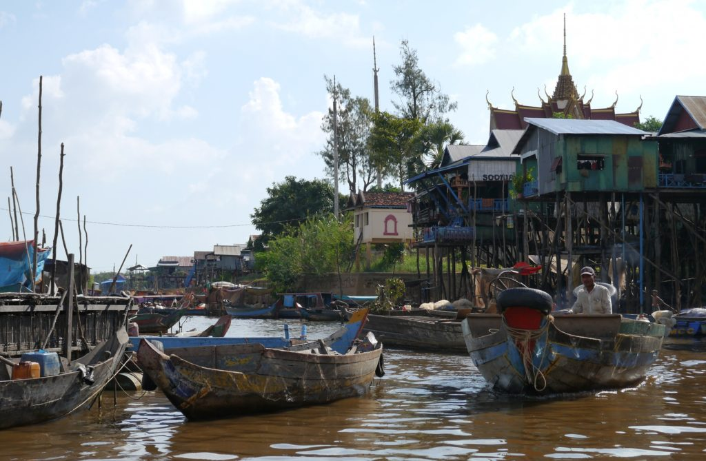 A boat chugs through Kampong Phluk commune, close to Tonlé Sap lake