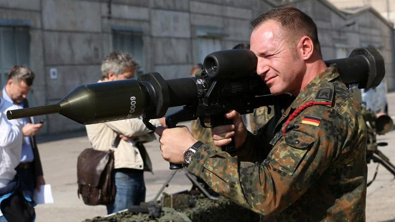 A member of the German army Bundeswehr presents a weapon which is part of a military aid for Iraq during a press event in Waren, northeastern Germany,