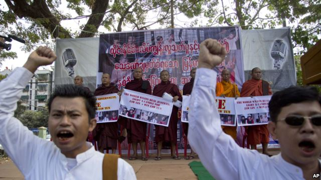 Myanmar nationalist Buddhist monks display placards as demonstrators shout slogans during a protest rally against a Thai court's verdict sentencing two Myanmar migrant workers to death, in Yangon,