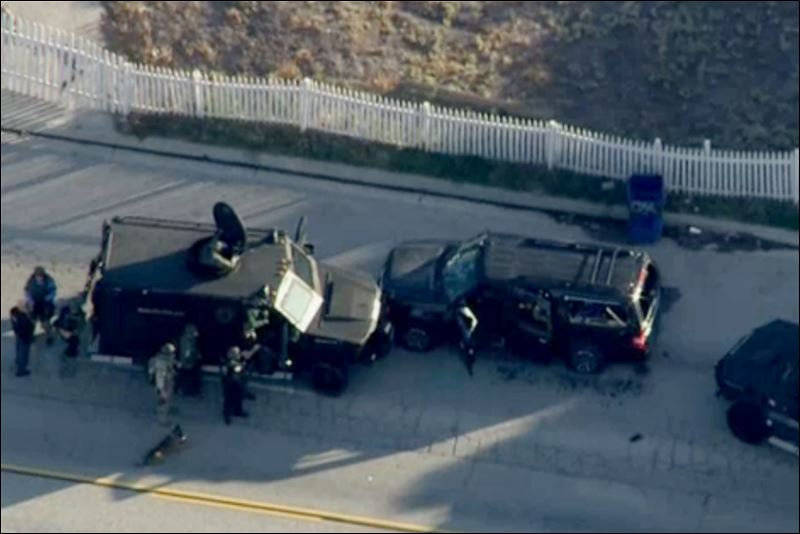 Armored vehicles surround an SUV following a shootout in San Bernardino, Calif., Wednesday