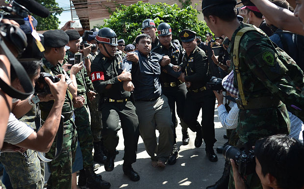 Sirawith Seritiwat (C), an anti-coup activist is taken away by security officials at Ban Pong train station in Ratchaburi province, Thailand Photo: Wasawat Lukharang