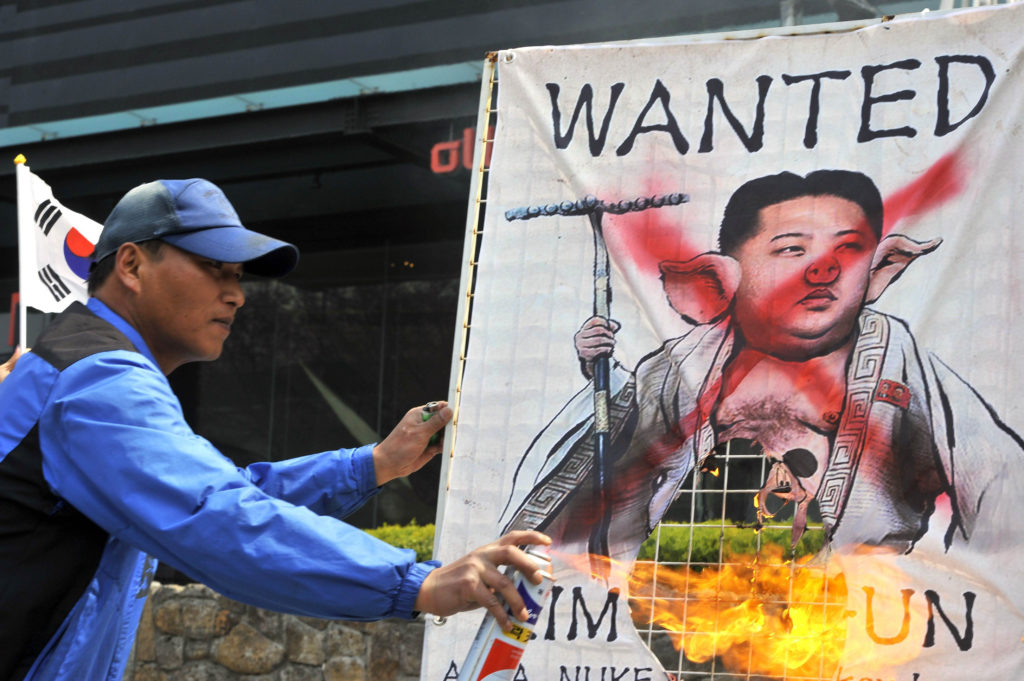 A South Korean activist burns a placard showing a caricature of North Korean leader Kim Jong-Un during an anti-North Korea rally in Seoul