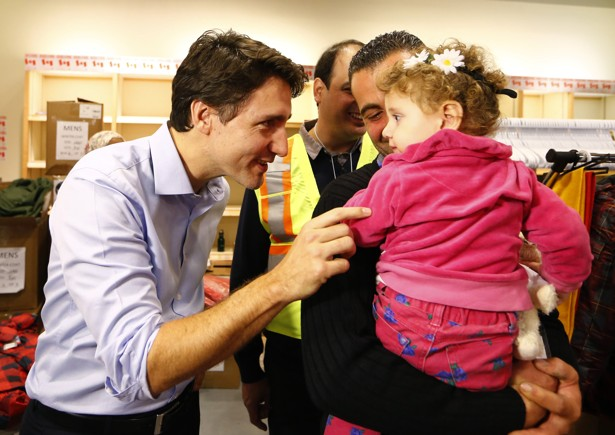 Syrian refugees are greeted by Canada's Prime Minister Justin Trudeau (L) on their arrival from Beirut at the Toronto Pearson International Airport in Mississauga, Ontario, Canada